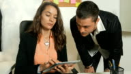 Two young adults man and woman office workers or colleagues looking at tablet and discussing a business project