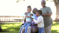 Two young African American children run to grandfather