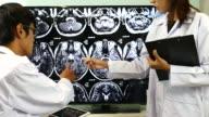 Zwei junge asiatische Ärzte diskutieren Krankheitsfall in Krankenhäusern