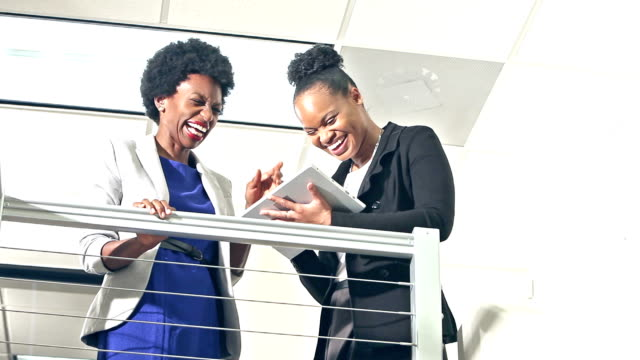 Two young black businesswomen with tablet computer
