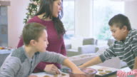 Two young brothers making making christmas cookies with their mom on christmas