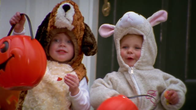 Two young children in Halloween costumes sit on a step.