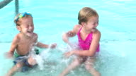 Two young children splashing each other in swimming pool