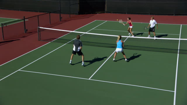 SLO MO, WS, HA, Two young couples playing doubles tennis, Santa Barbara, California, USA