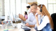 HD Two young coworkers using smart phone in modern office