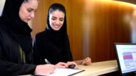 Two young Emirati women filling a form at reception