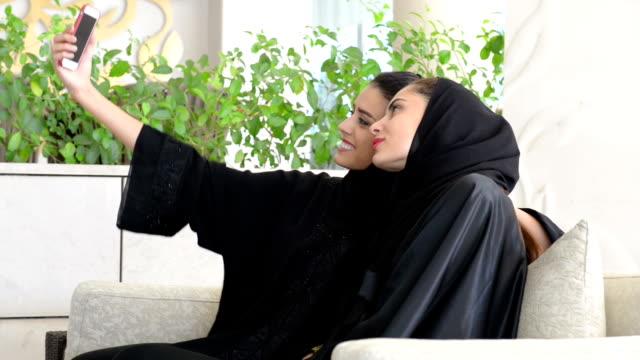 Two young Emirati women taking a selfie