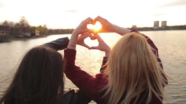 Two young females making heart shape with their hands.