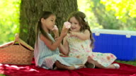 Two young girl friends eat ice cream