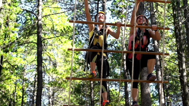 Two young girls climbing a rope ladder