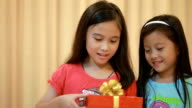 Two young girls opening Christmas gift