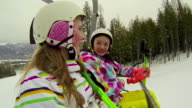 Two young girls riding chair lift at ski hill