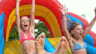 SLO MO Two young girls sliding off inflatable water slide
