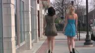 Zwei junge Mädchen Frauen zu Fuß. Sexy kurze Kleider. Einkaufsmöglichkeiten.