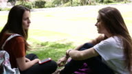 Two young Latina women relax in urban park, talking