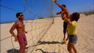 Two young men and a woman play beach volleyball.