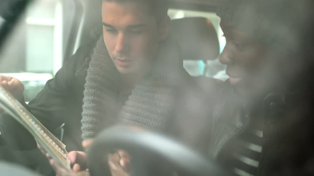 CU zwei junge Männer diskutieren mit Karte im Auto