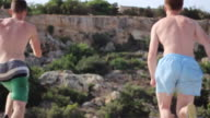 Two young men jumping off a boat into the sea in Malta. - Slow Motion - Model Released - HD