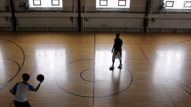 WS Two young men playing basketball against each-other inside  gymnasium / Minneapolis, Minnesota, United States