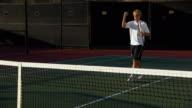 WS, PAN, Two young men shaking hands above tennis net, Santa Barbara, California, USA