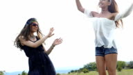 Two young women dancing on grass,slow motion