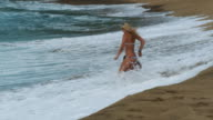 two young women getting hit by a wave