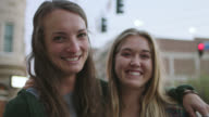 MS SLO MO. Two young women look at each other and laugh on downtown city street corner.