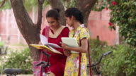 Two young women reading books, Haryana, India