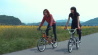Two young women riding bicycles in a rural area