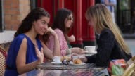 Two young women sit outside a cafe and enjoy coffee and croissants.