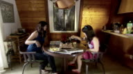 WS Two young women sitting and playing chess at dining room table/ Man running past and squirting them with water gun/ Los Angeles, California