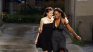 Two young women slow motion having fun in the city