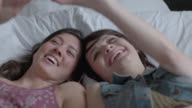 Two young women take selfies with smartphone in bed