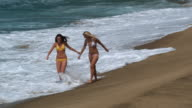 two young women walking on the beach