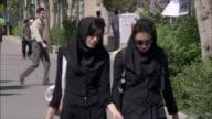 MS Two young women walking towards University building, Tehran, Iran