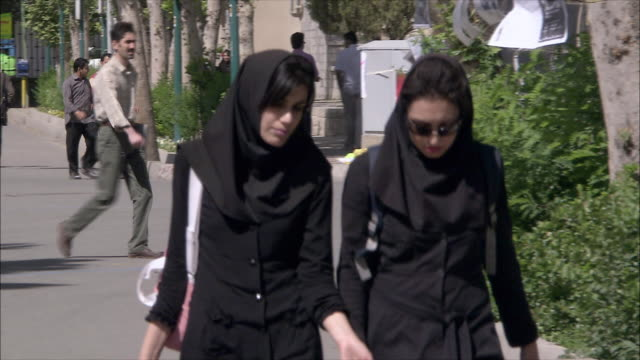 MS Two young women walking towards University building, Tehran, Iran