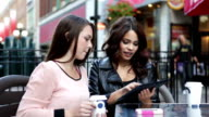 Two young women with digital tablet at outdoor cafe