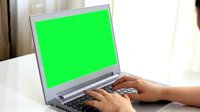 Typing on notebook computer with green screen at home