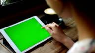 Tippen auf Tablet im Kaffee shop mit grünen Bildschirm