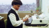 MONTAGE Typist using a desk terminal microcomputer in an office / United Kingdom