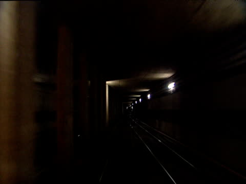 U-Bahn underground train leaving platform and racing through tunnel before stopping at next station Munich