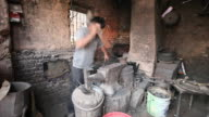 Uighur Muslim Blacksmith pounds metal