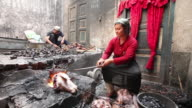 Uighur Muslim woman grilling lamb heads
