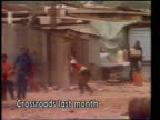 Uitenhage shooting UPITN February 1985 Crossroad MS White jeep towards spraying tear gas LMS Black people standing in front of shacks PAN RL as throw...