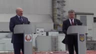 Ukrainian President Petro Poroshenko and Belarussian President Alexander Lukashenko deliver statements in front of the new protective shelter over...