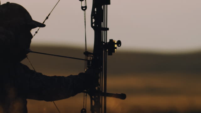Ultra Slow-Motion, 200 Bilder pro Sekunde, der eine Hintergrundbeleuchtung Bowhunter feuert seinen Bogen auf seinem Ziel im schönen Sonnenuntergang Leben.