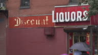 Umbrella tops cross the frame underneath a nondescript discount liquor store sign as it rains in Brooklyn.