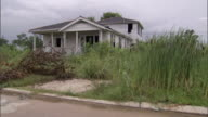 Uncut grass and an abandoned house are on a street flooded after Hurricane Katrina..