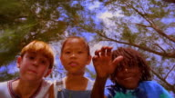underwater low angle MS blond boy, Black boy + Asian girl putting hand on water over camera causing ripples