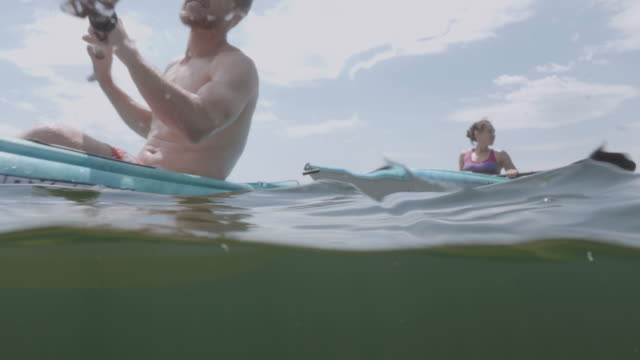 4K SLO MO: Underwater view of a man and woman kayaking